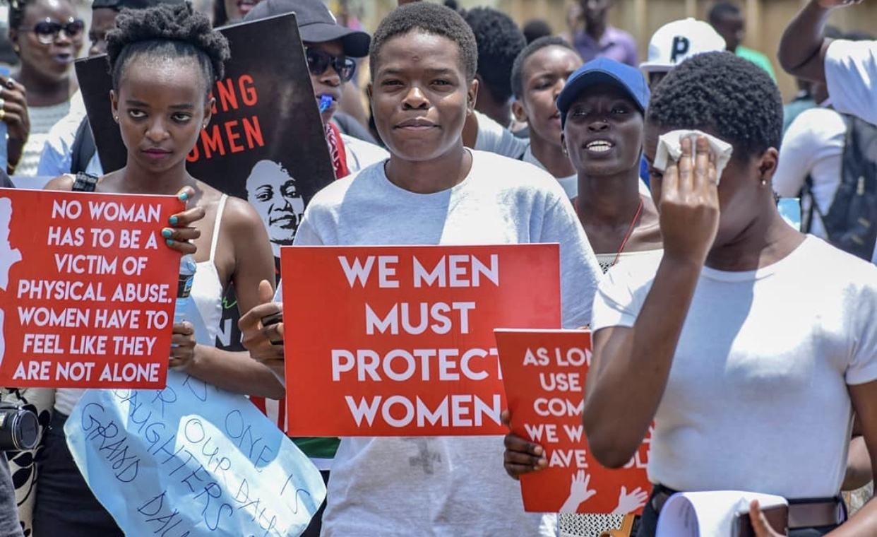 """Africans marching with signs such as: """"We men must protect women"""" and """"No woman has to be a victim of physical abuse. Women have to feel like they are not alone."""""""