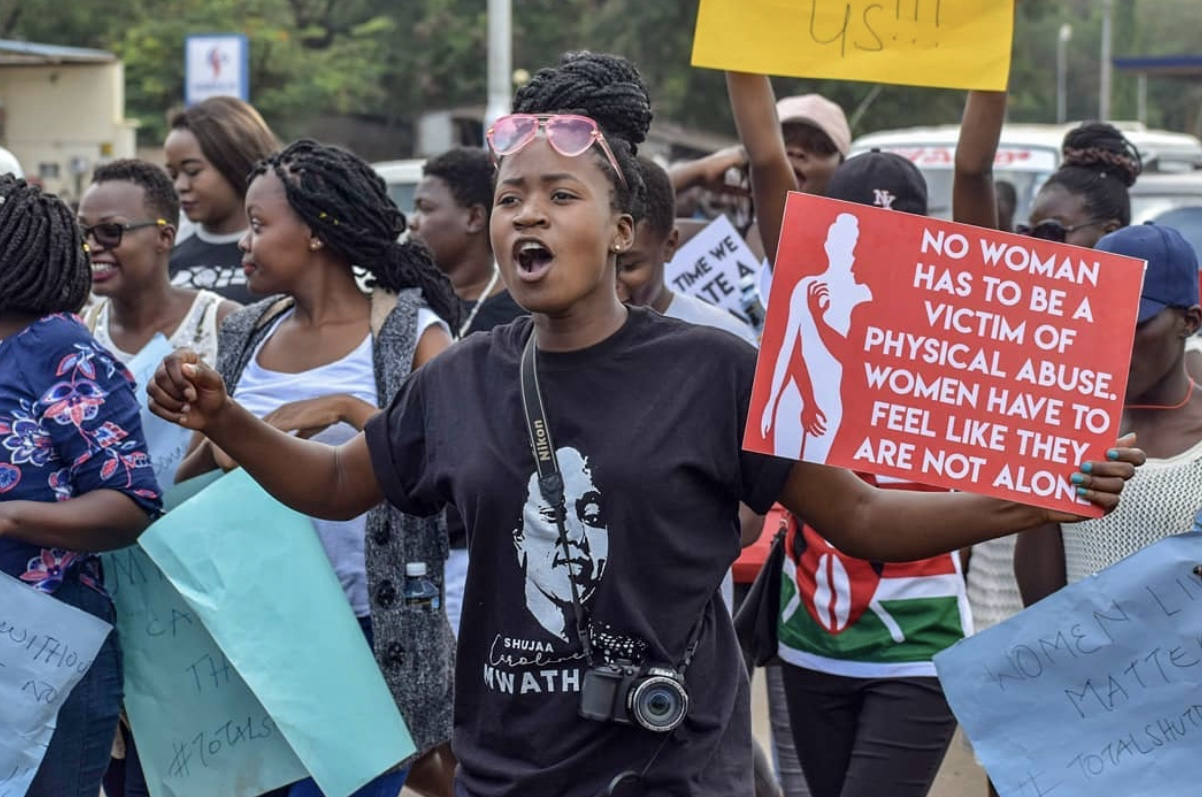 """African woman chanting while marching with the following sign: """"No woman has to be a victim of physical abuse. Woman have to feel like they are not alone."""""""